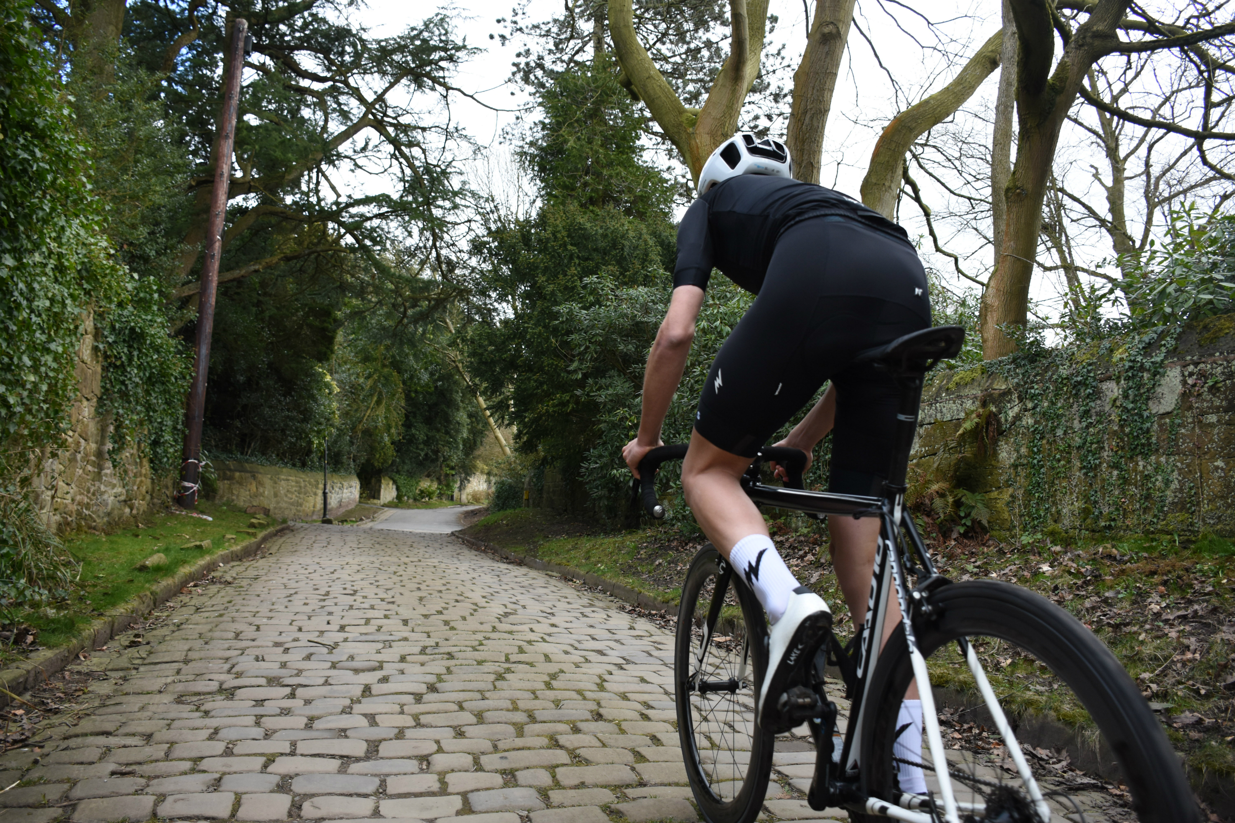 a cyclist riding on cobbles in the morvelo ss18 nth series range