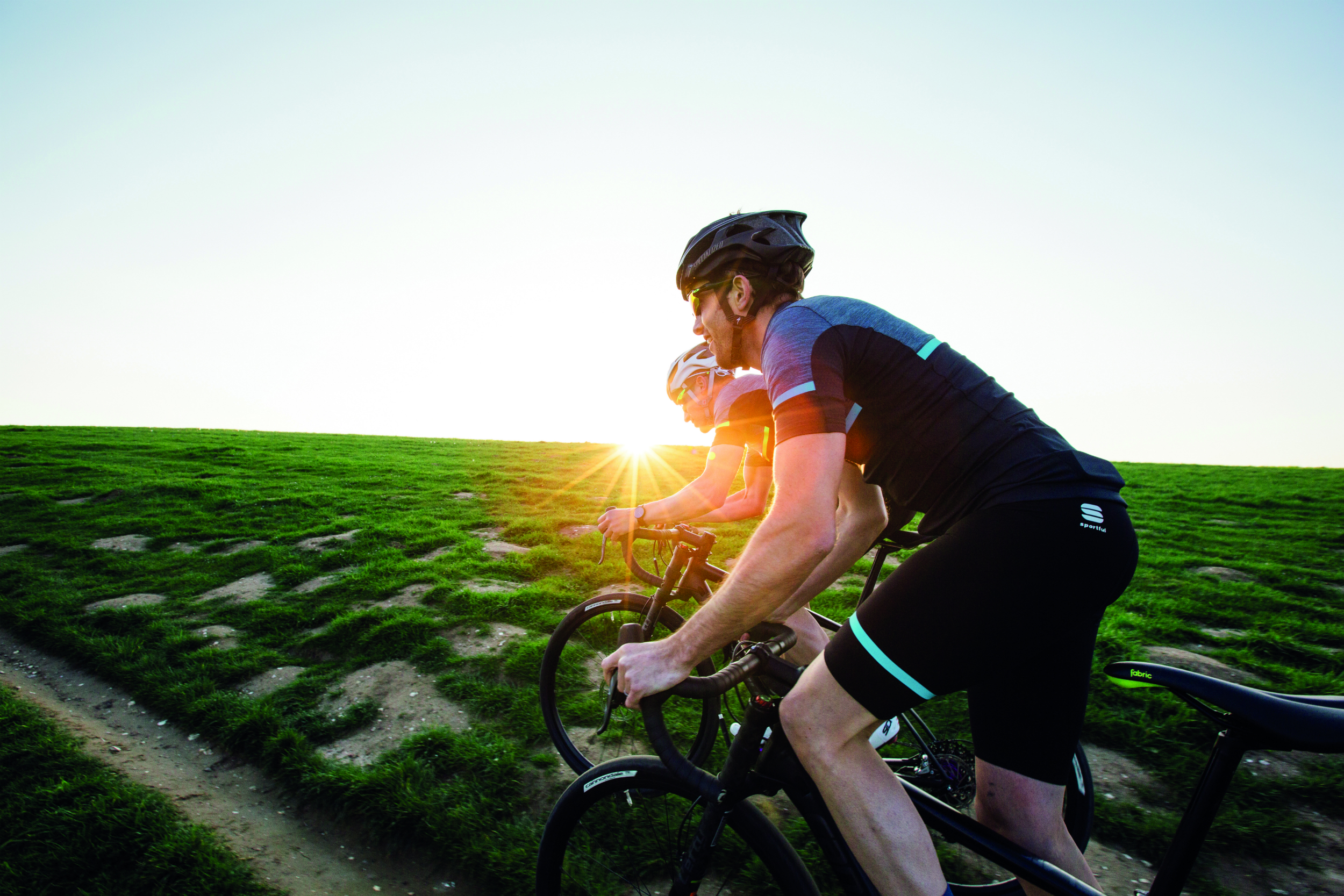 two cyclists riding off-road as the sun sets in giara cycling clothing