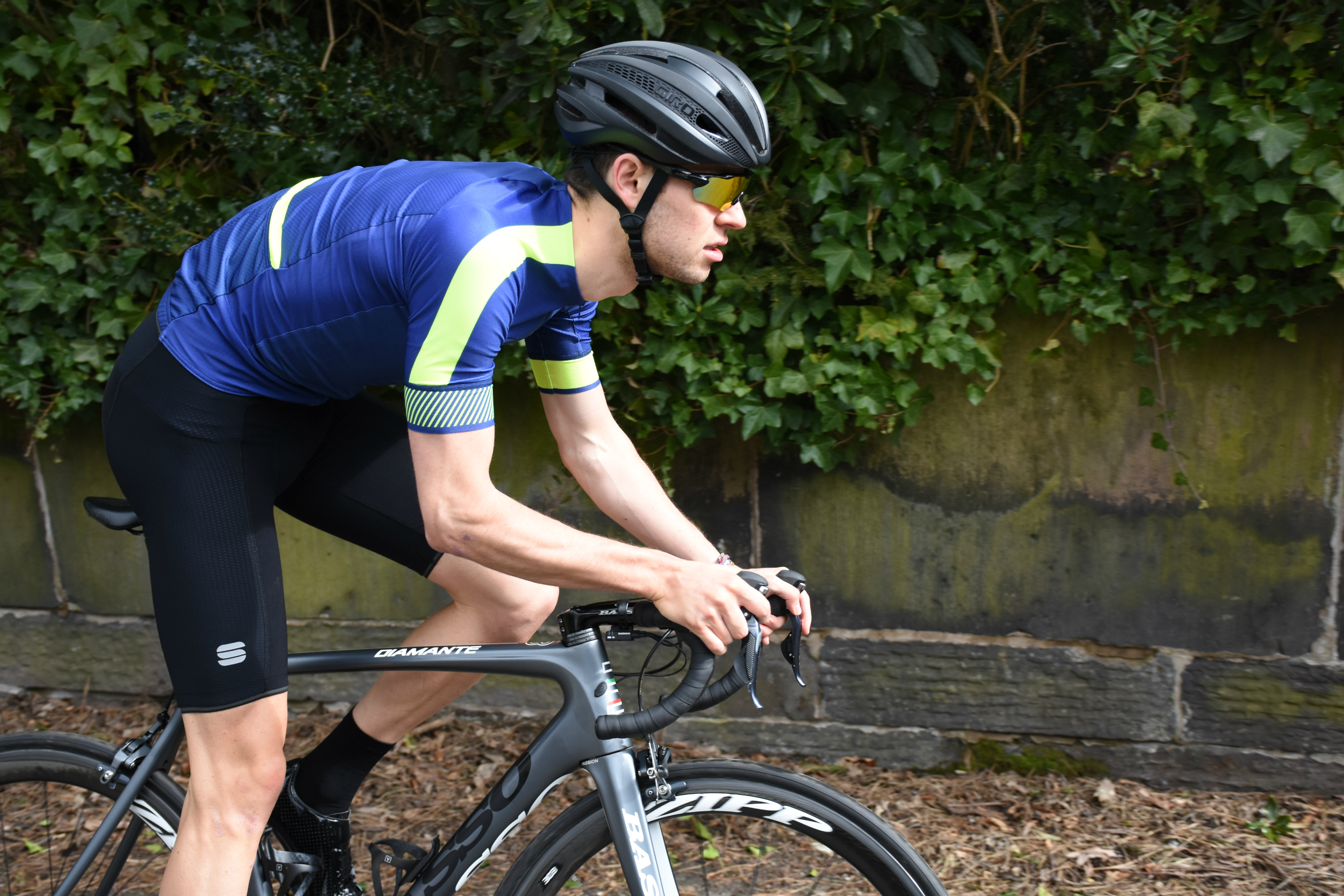 a cyclist out of the saddle in the sportful body fit pro evo blue and fluro jersey