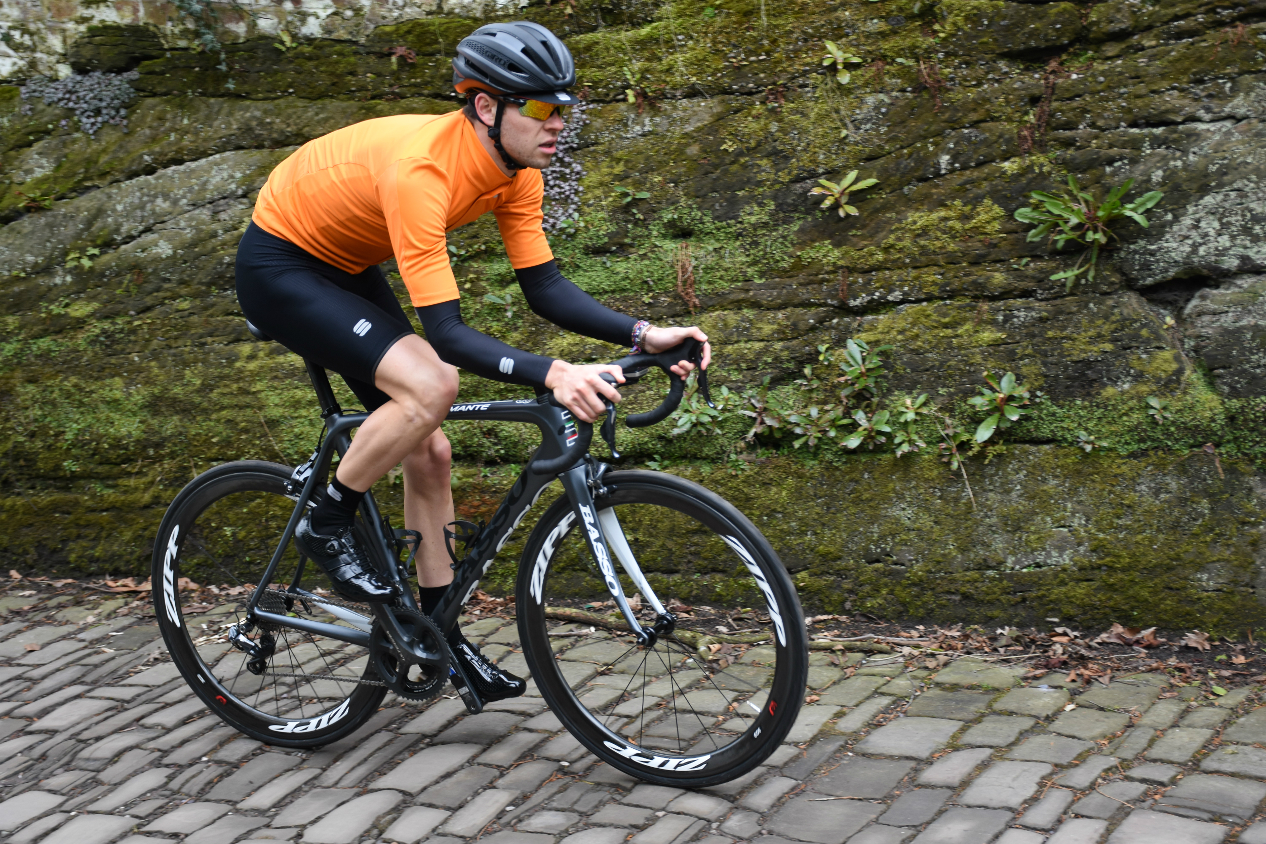 a cyclist riding on cobbles in the fiandre light jersey in bright orange