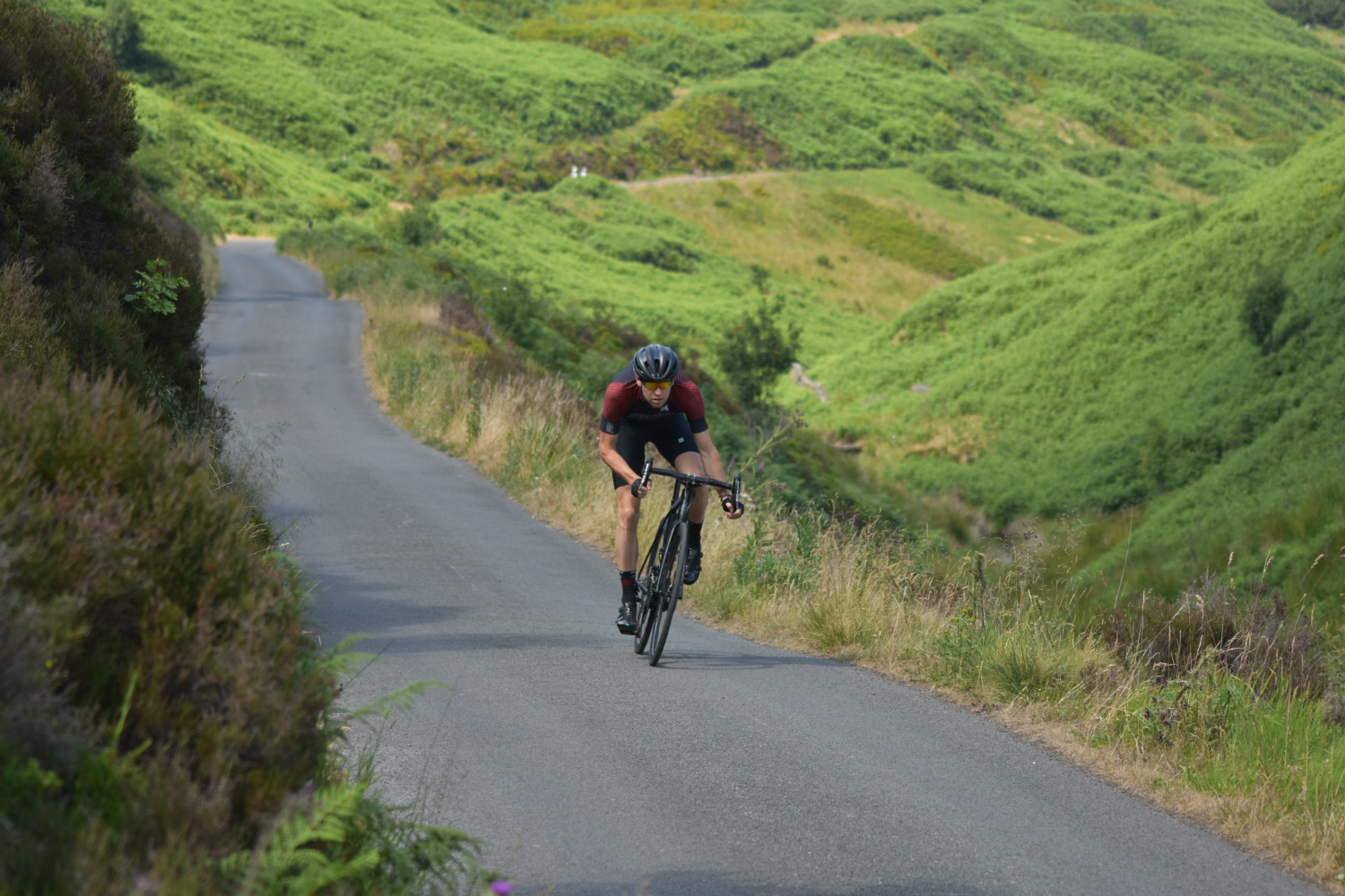 a cyclist sprinting uphill in the drops