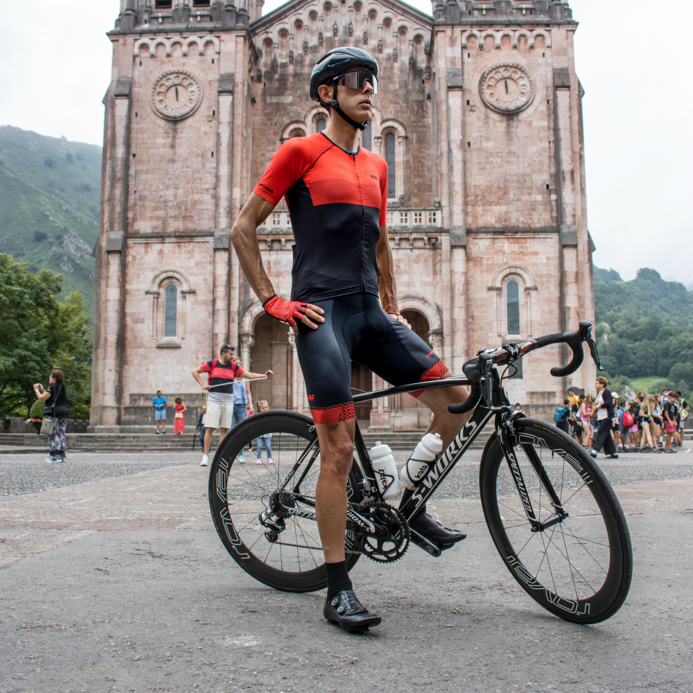 a cyclist wearing the kalas covadonga colletion stood infront of a church