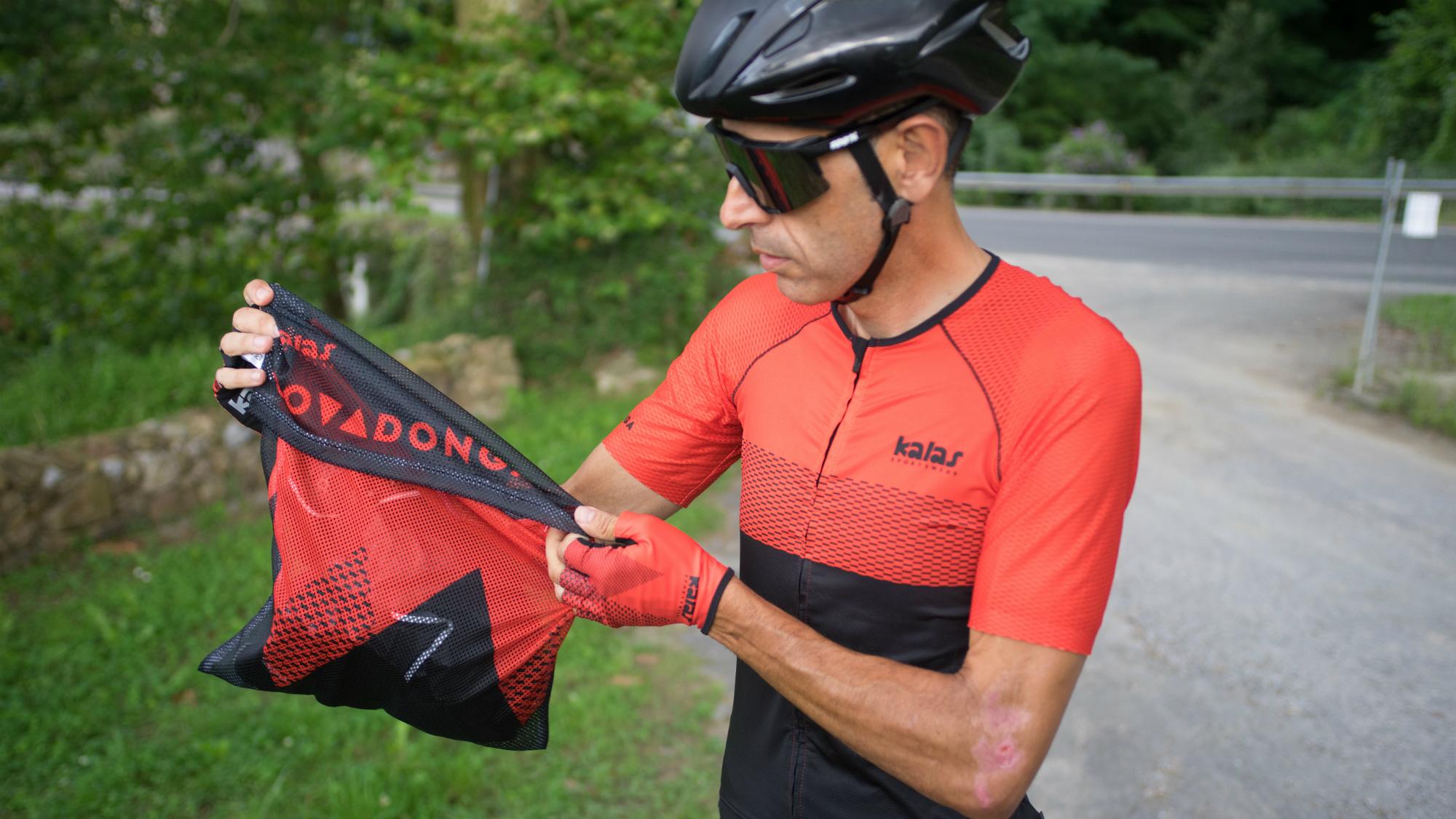a cyclist holding the kalas covadonga jersey