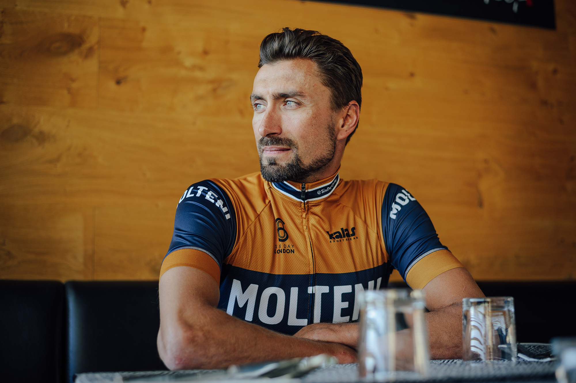 a cyclist sat at a table in the kalas molteni jersey.