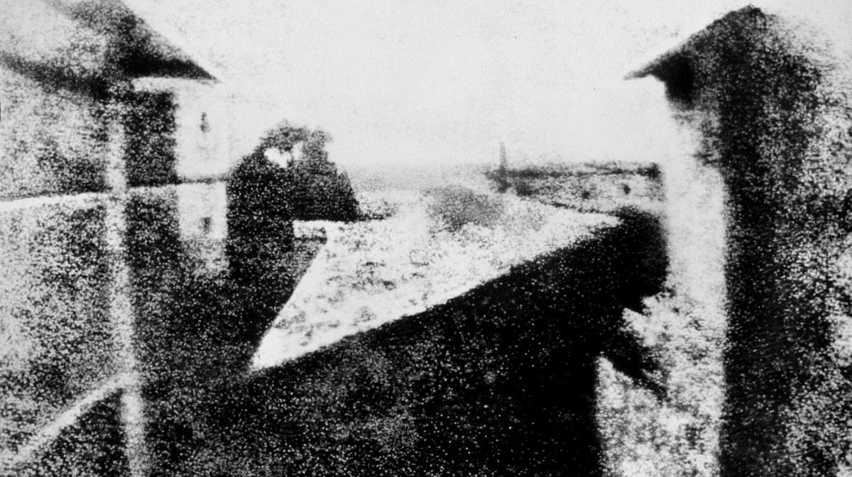 black and white image of a view from a window onto buildings and the surrounding countryside