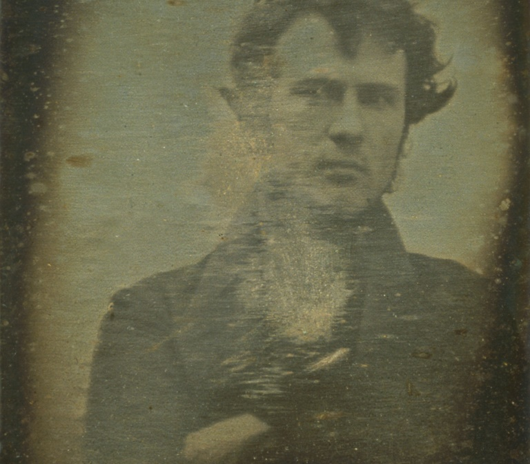 a sepia self-portrait of Robert Cornelius folding his arms