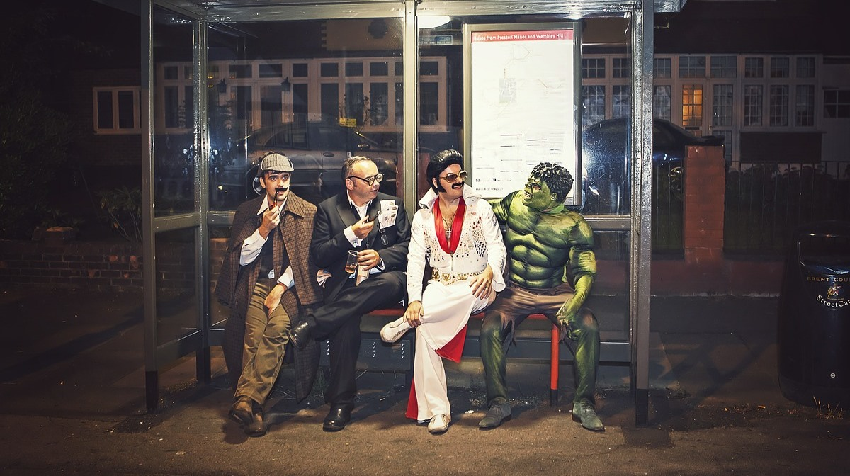 a man dressed in full sherlock holmes garb alongside other popular figures on a bus stop bench in a residential area at night