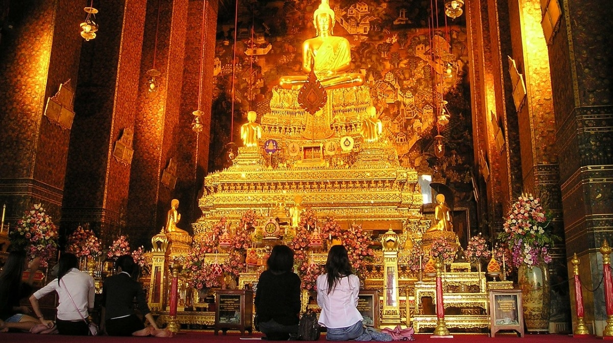 women looking up at golden buddha in bangkok temple