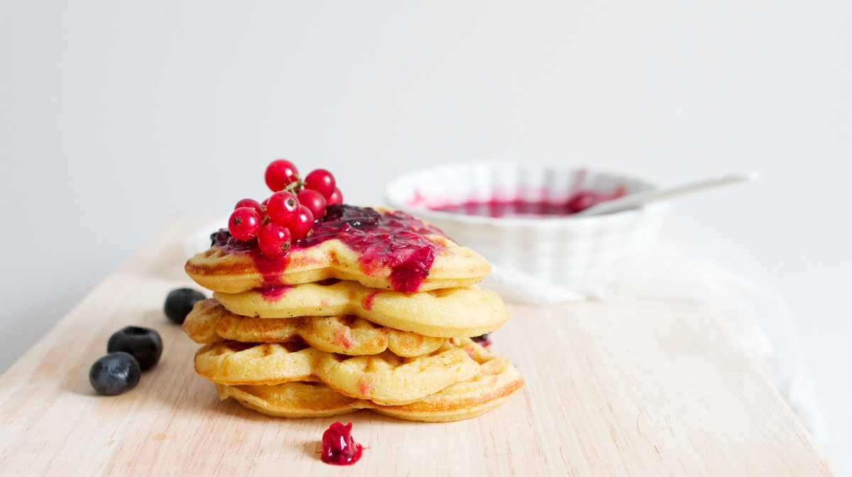 stacked pancakes with berry compote on top