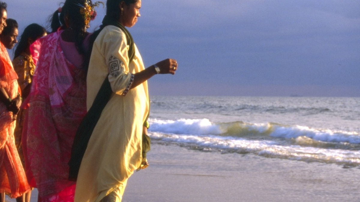 Goan women looking out onto the sunset at sea