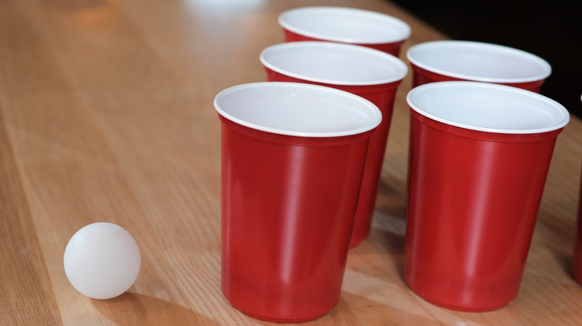 beer pong cups on table with ball