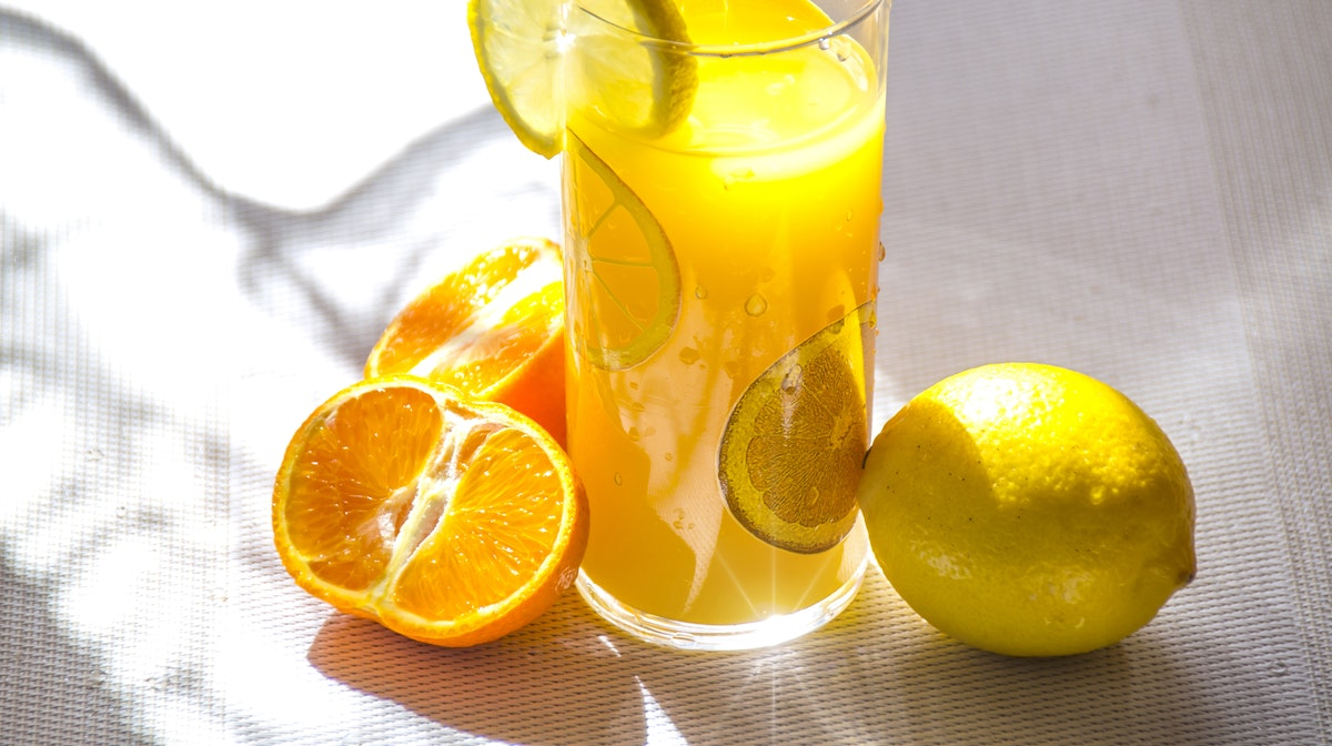 glass of orange juice and cut citrus fruits
