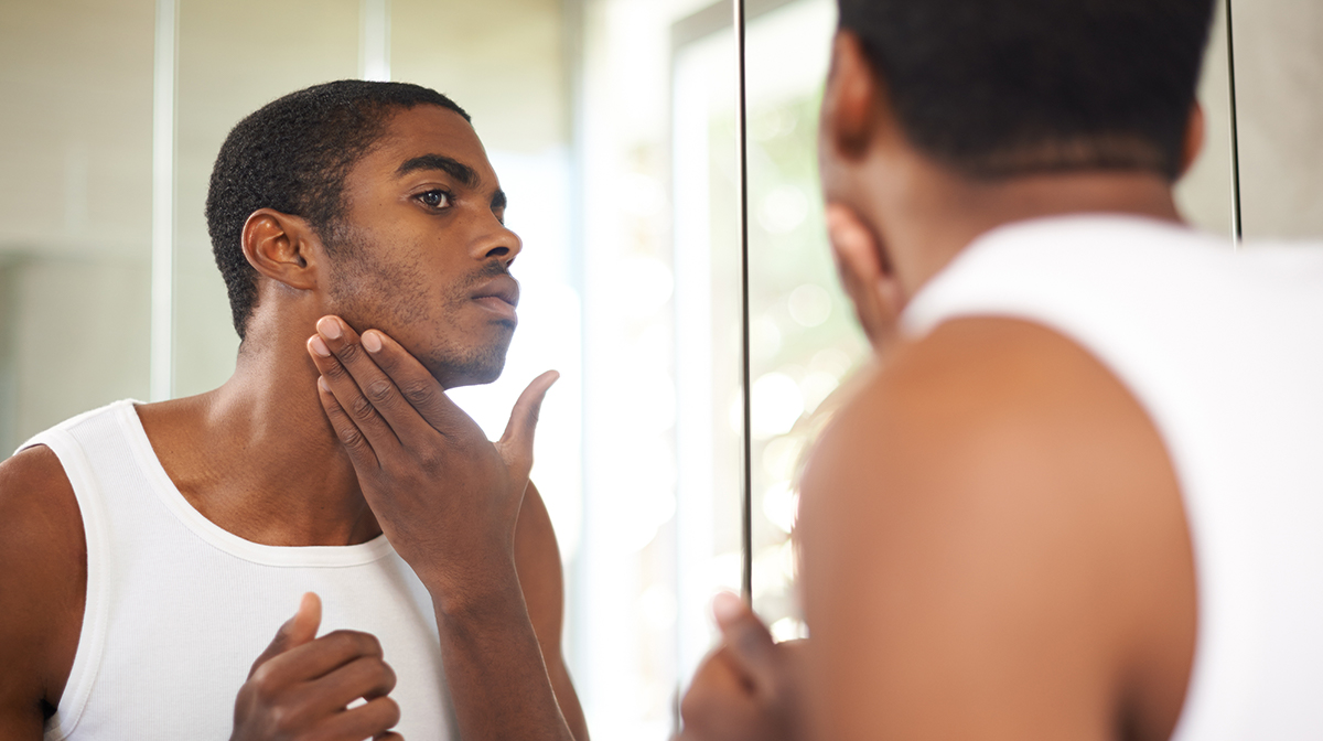 Man rubbing skin in mirror