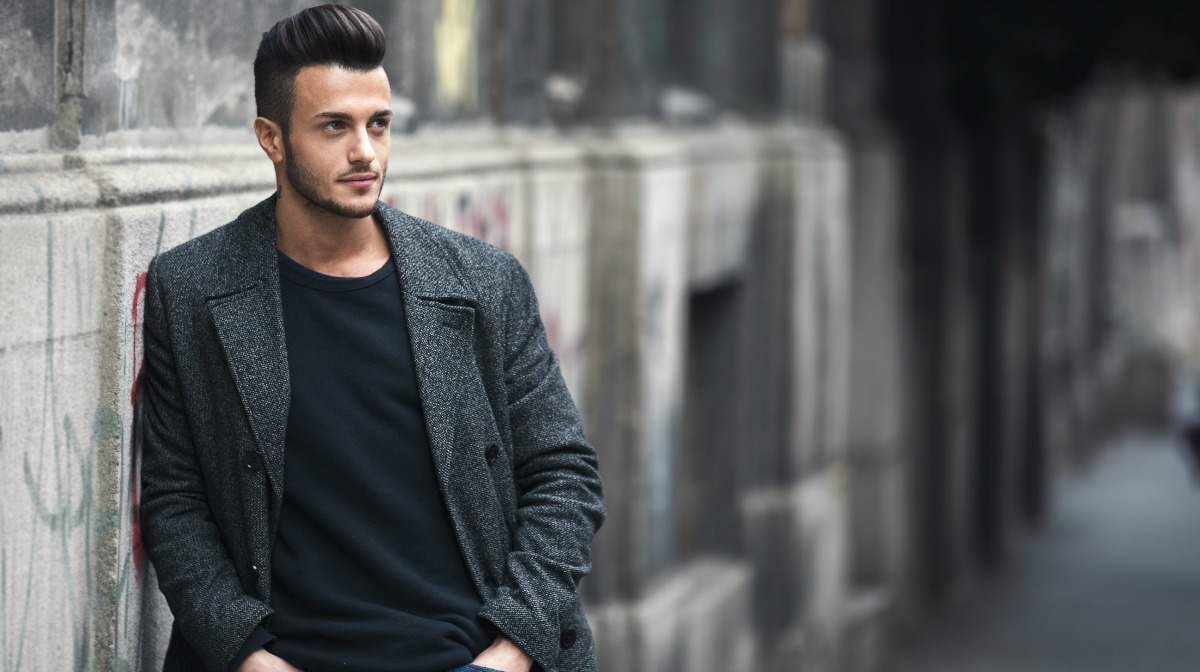 Man with quiff stood outside in street in front of wall