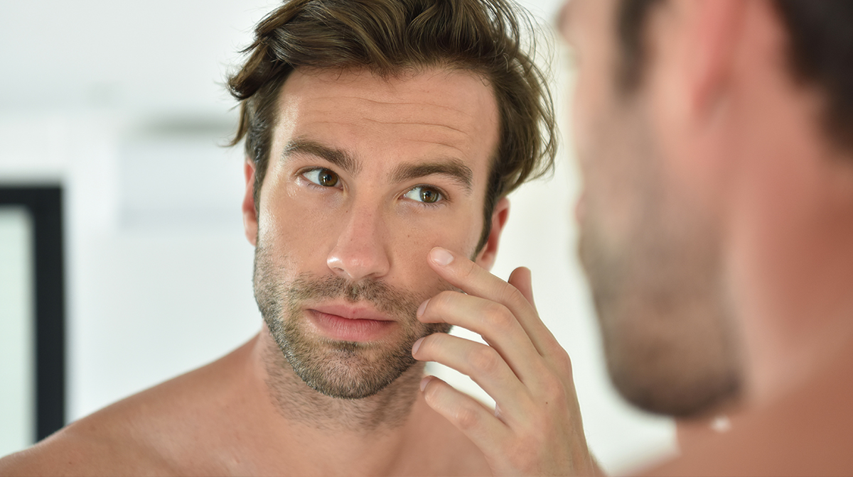Man in front of mirror touching cheek