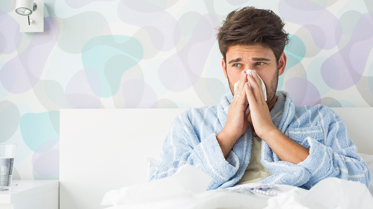 Sick man blowing nose in bed