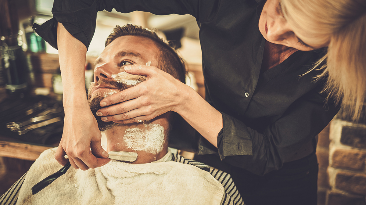 Man being shaved with cut throat razor