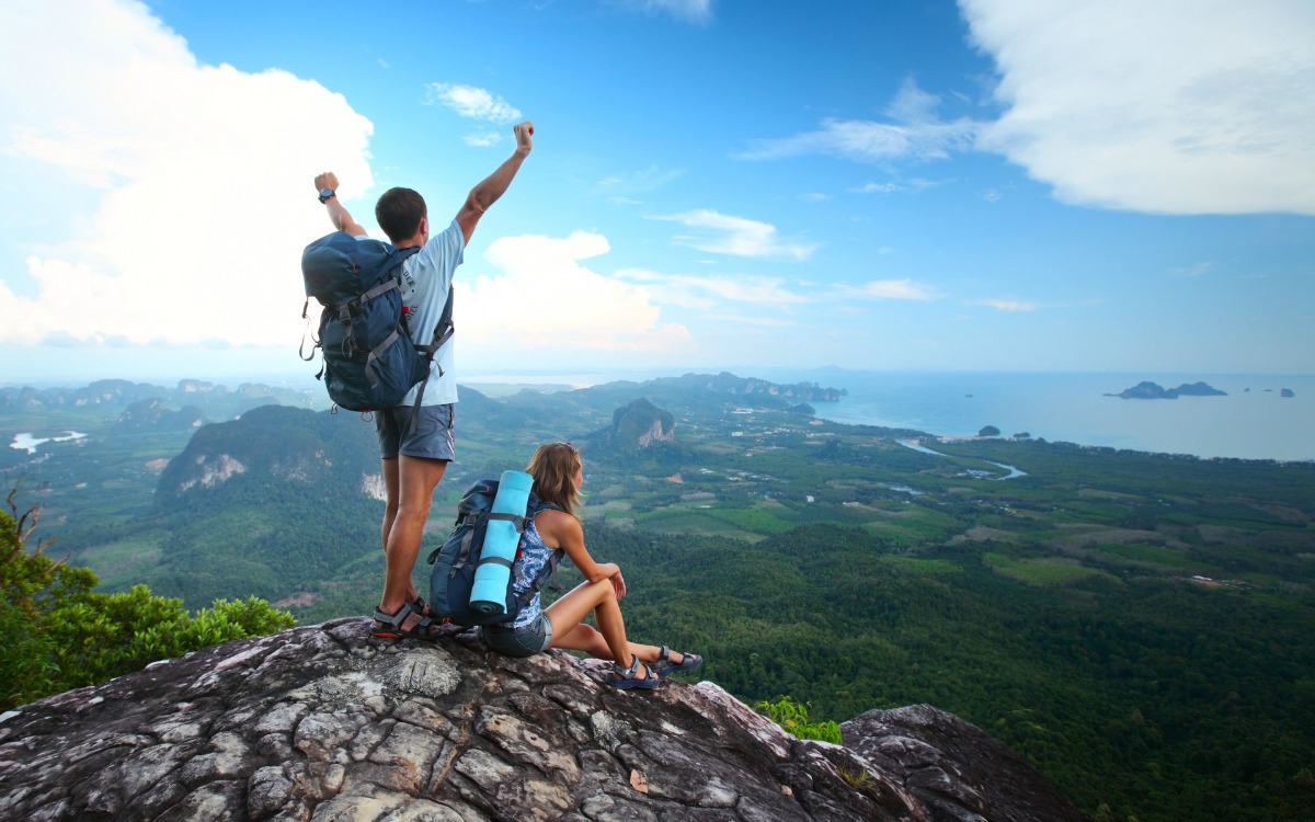 healthy man and woman on top of a mountain