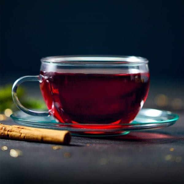 mulled wine water enhancers in glass mug with cinammon stick on side