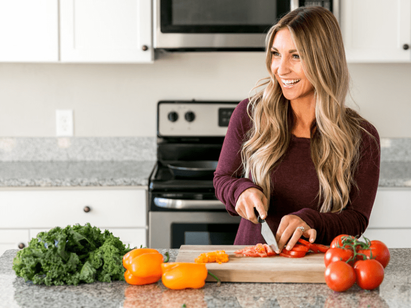 Mommy Trainer Bree slicing vegetables as part of her vegan meal prep