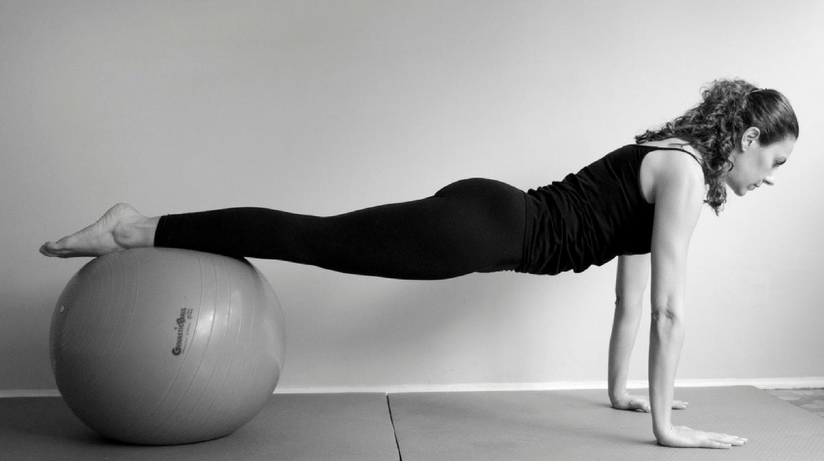 donna esegue il plank con fitball