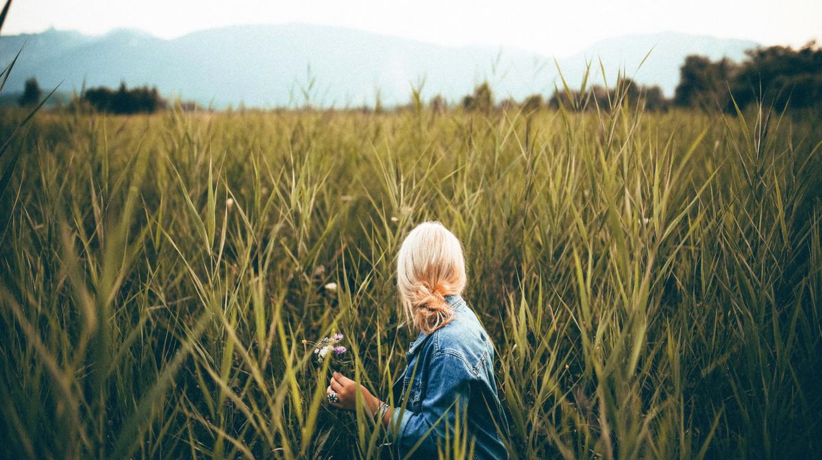 ragazza in un campo di grano: stare all'aperto aiuta a vivere sani!