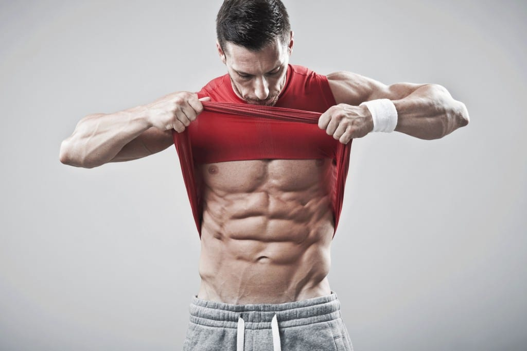 man in red gym tank top showing off his 6 pack