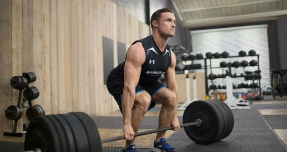 man in black gym tank and shorts performing a deadlift with barbell