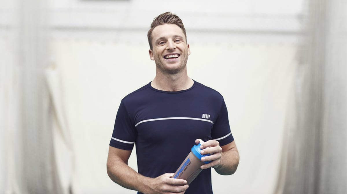 man in gym clothing smiling and holding a myprotein protein shaker bottle