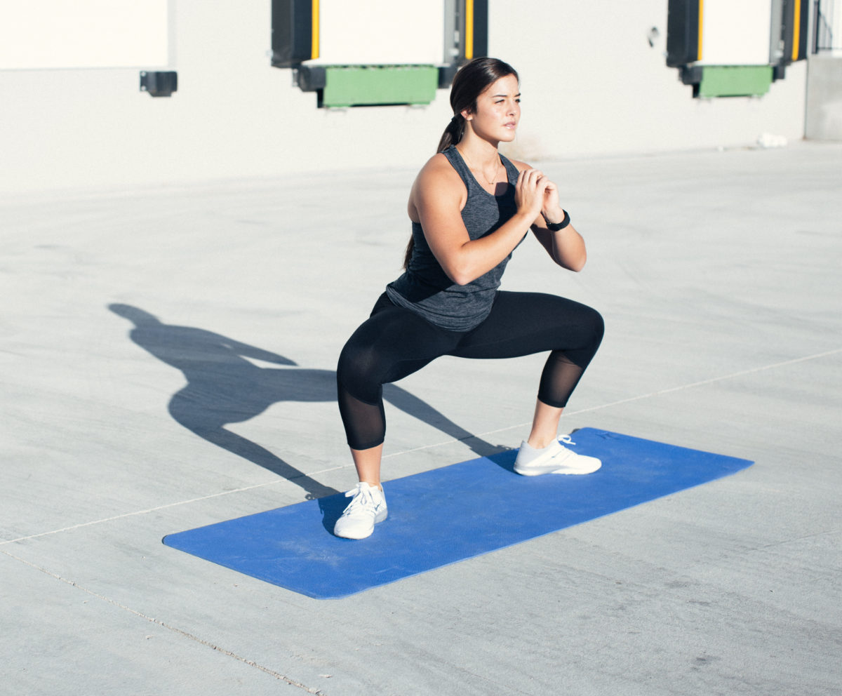 woman in idealfit gym clothing doing a sumo squat