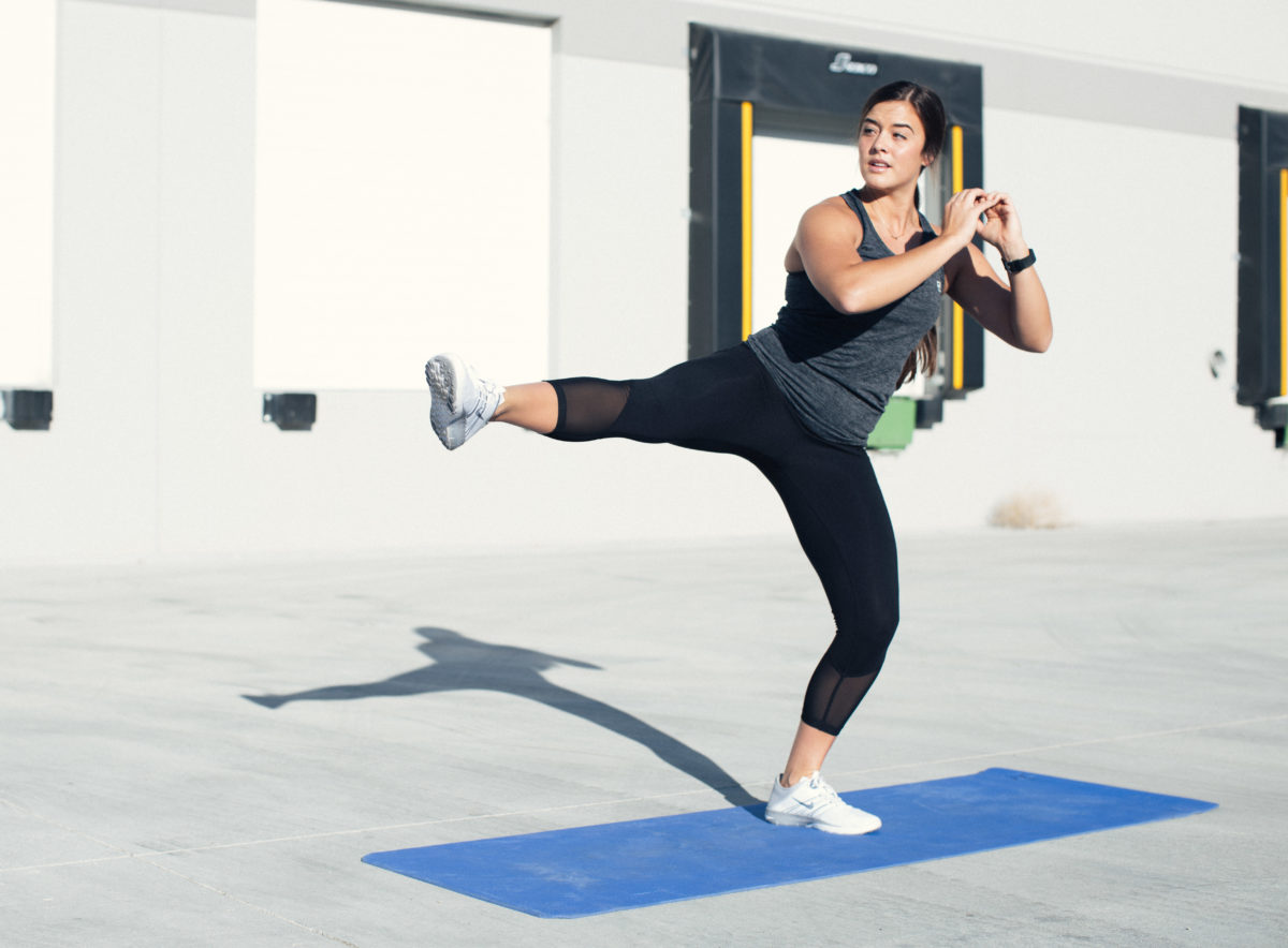 woman in idealfit gym clothing doing a side kick