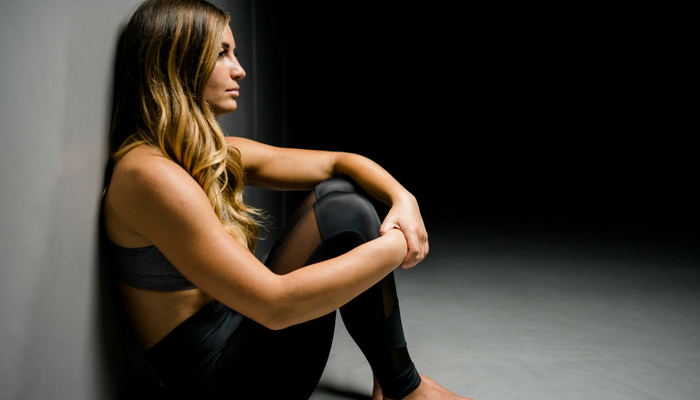 female athlete sitting in the dark