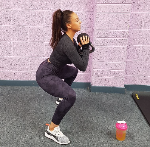 Girl doing SUmo Squat in the gym