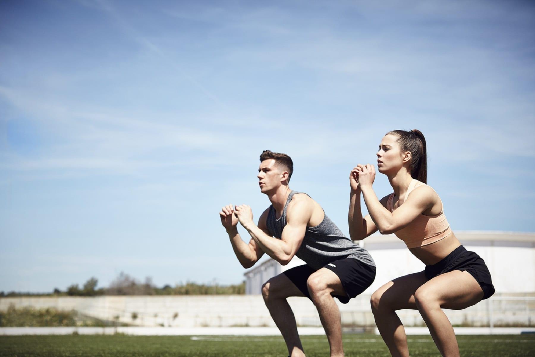 Mann und Frau machen Squats