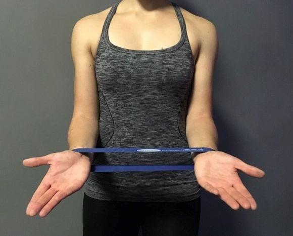 3) Das Theraband wird um die Handgelenke angebracht, dabei werden, anschließend die Handflächen auseinander zur Seite bewegt.
