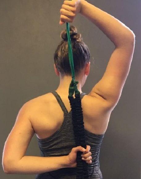 5) Zur Mobilisation des Schultergürtels wird hinter dem Rücken wird ein Tube oder Seil gefasst und durch Zug das Schultergelenk nach oben und unten mobilisiert.