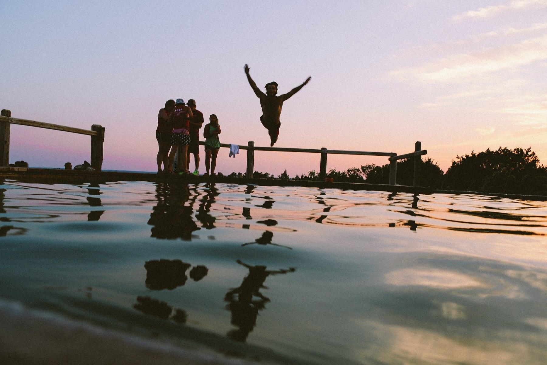 Mann springt in einen See