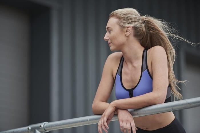 mujer apoyada con los brazos sobre una barra