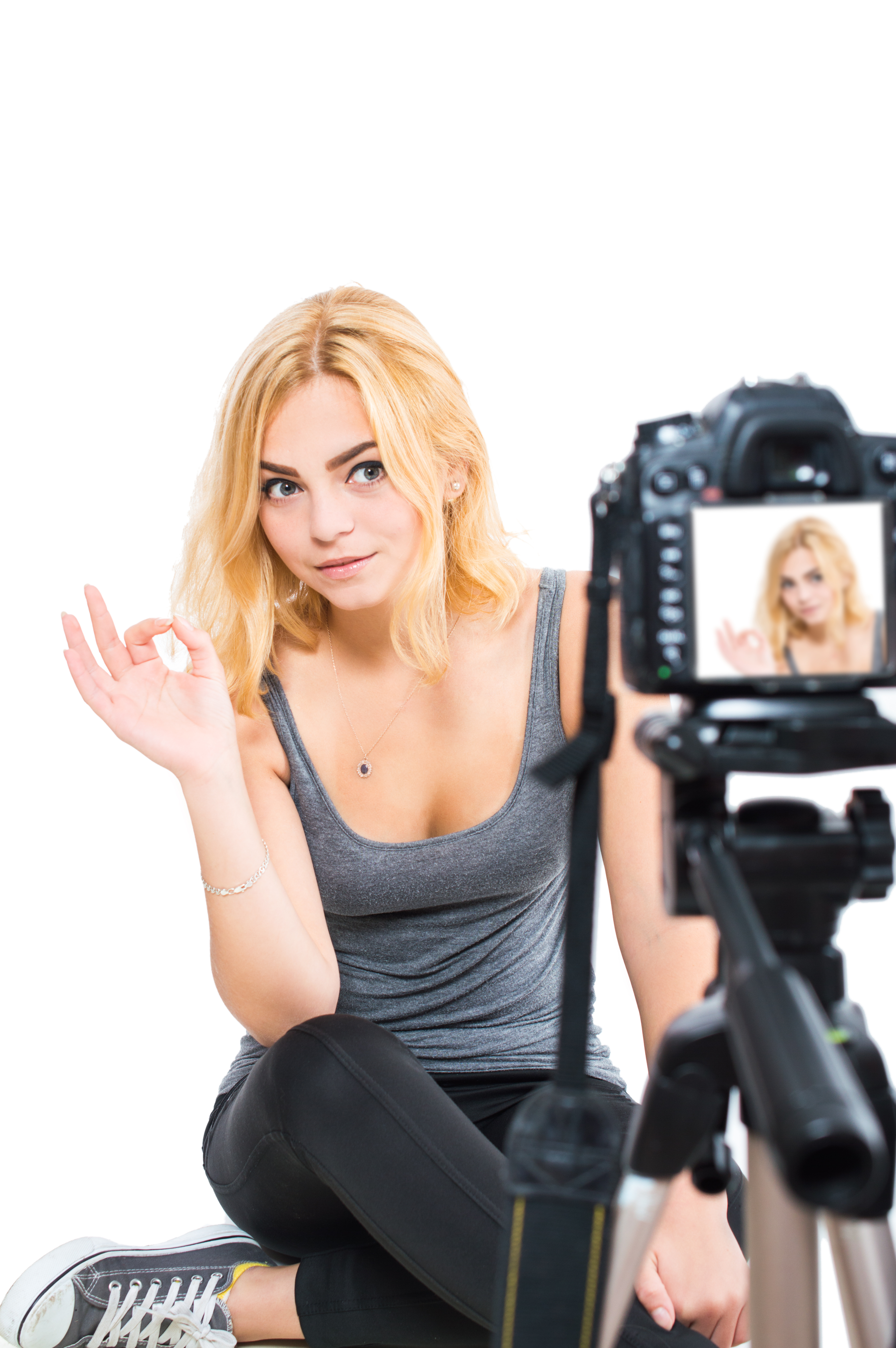 Woman blogger relieves herself on camera. On white, isolated background.