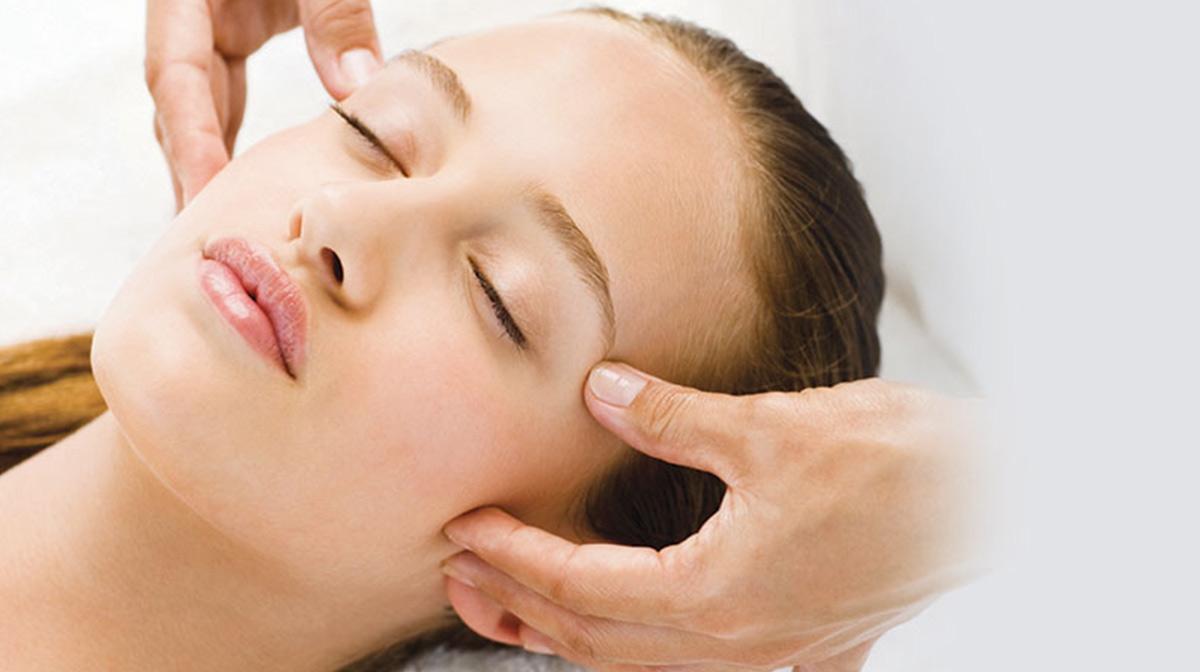 A woman closing her eyes enjoying a facial massage spa treatment