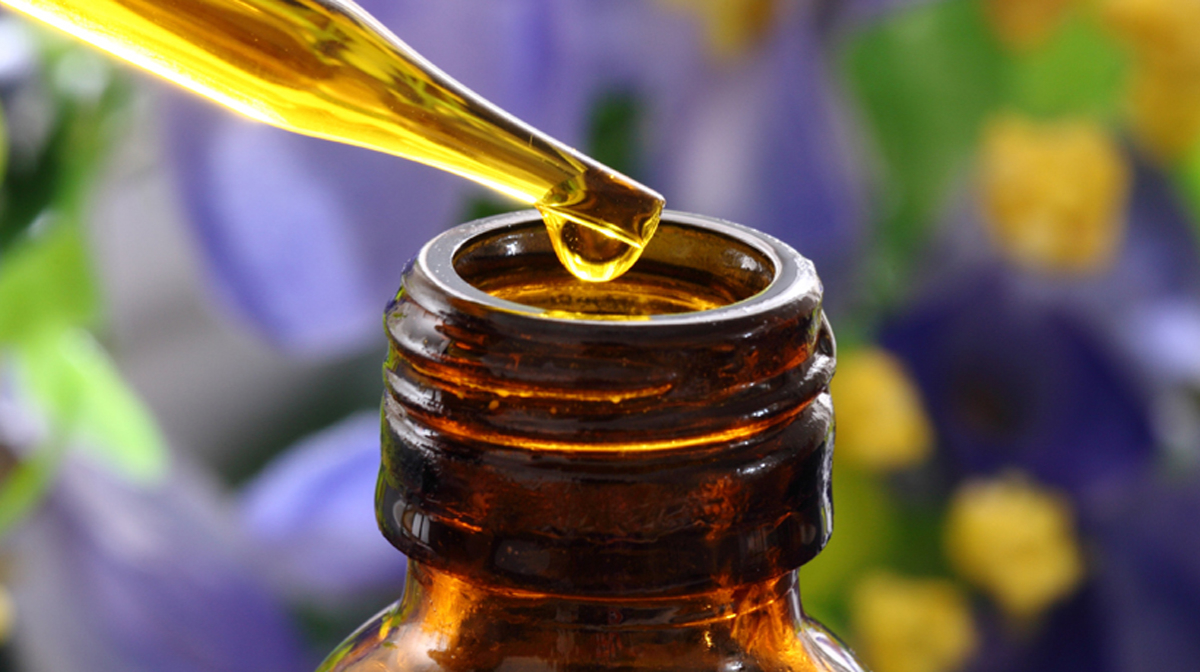 Essential oils, oil dropping into a bottle