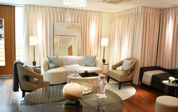 Relaxing lounge with cream coloured sofas and curtains and lots of cushions