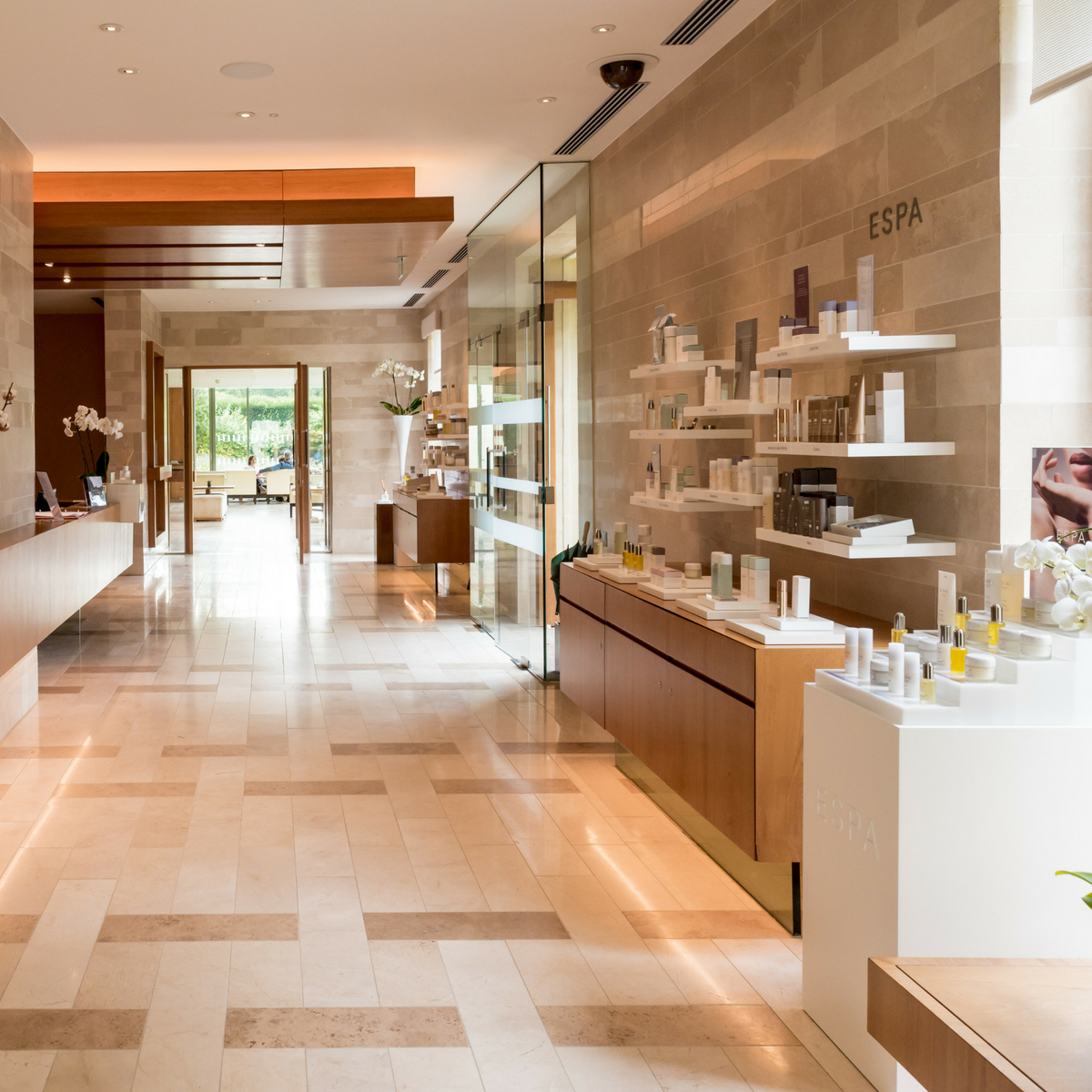 Pristine marble spa corridor with walls covered in products.