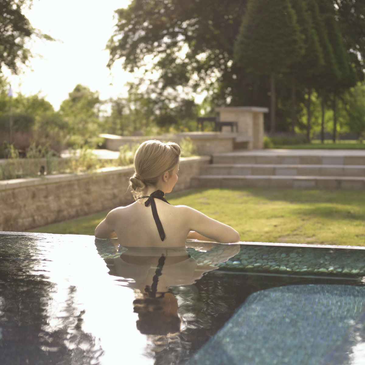 Lady in an outdoor pool overlooking the gardens of Lucknam Park on a sunny day