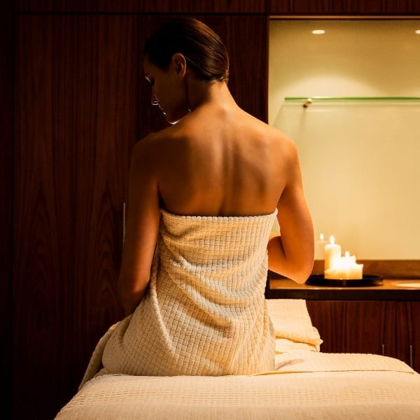 A woman sat on the therapist bed in a towel before a spa treatment