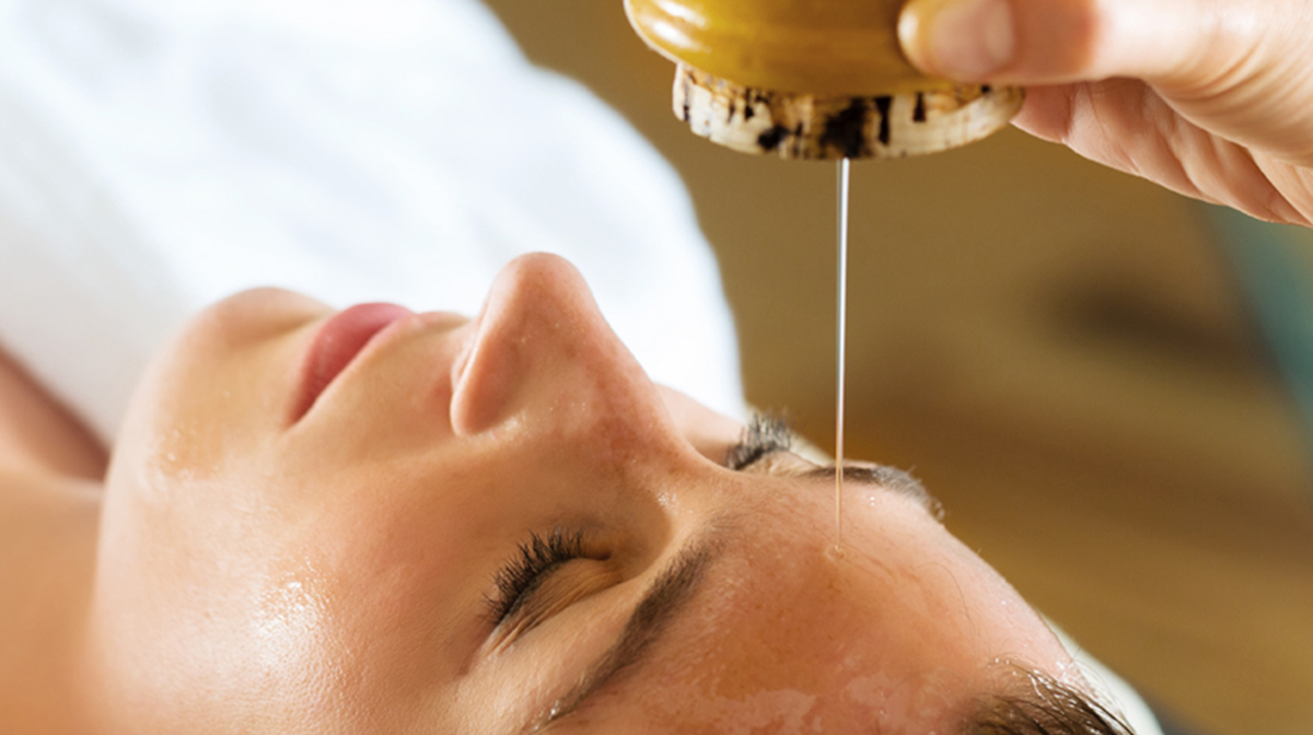A woman smiling enjoying a back exfoliation spa treatment