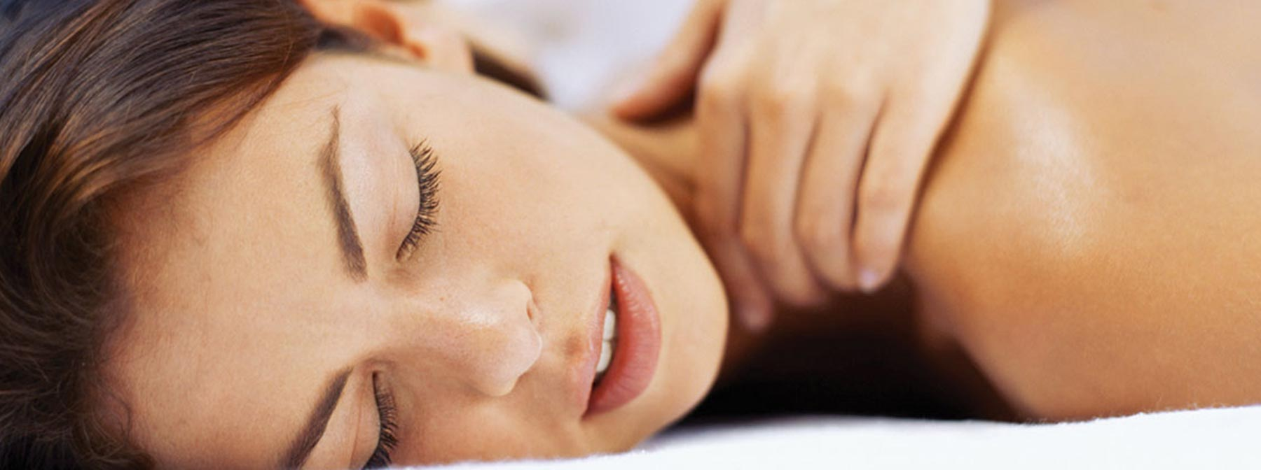 A woman lying on a bed enjoying a neck massage spa treatment