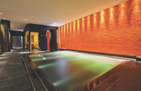 Indoor pool beside a brick wall in ESPA Riga