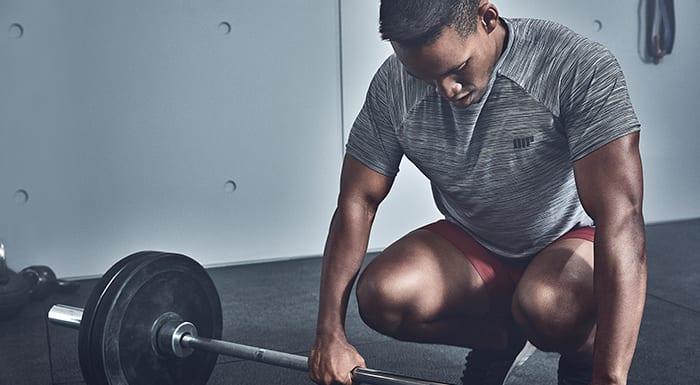 male athlete preparing to deadlift barbell