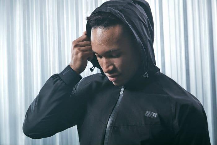 Man in black hooded jacket looking down
